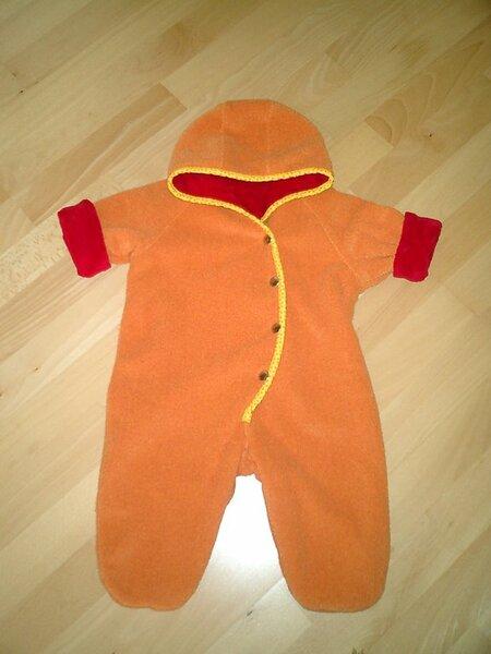 Babyoverall in Größe 74. Außen Boucle-Fleece in orange, innen Sommerfrottee rot. Der Rand ist eingefasst mit einem gelben Schrägband mit orangenen Tupfen.