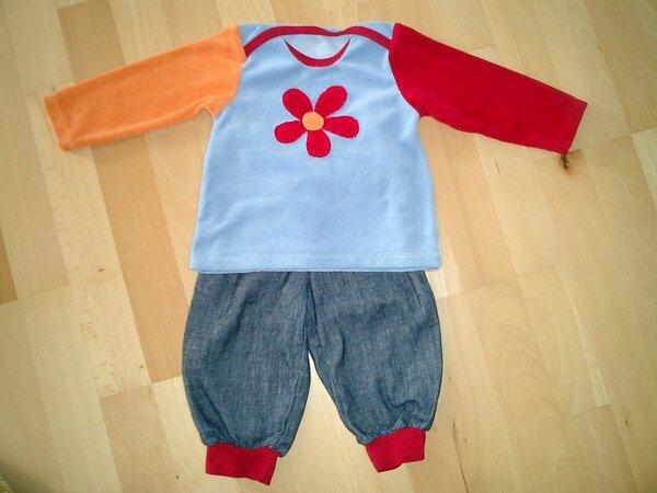 Babykombination: Shirt aus Sommerfrottee (blau, orange, rot) mit Blumen-Applikation und amerikanischem Halsausschnitt. Hose aus weichem Jeansstoff mit roten Bündchen am Bauch und an den Beinen.
