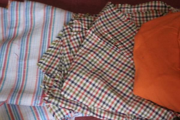 Längsgestreifter Stoff, flatterig, vermutlich keine BW, oder nur zum Teil(?) karierter Stoff, Material unbekannt, dünn, leicht glänzend oranger Piquestoff