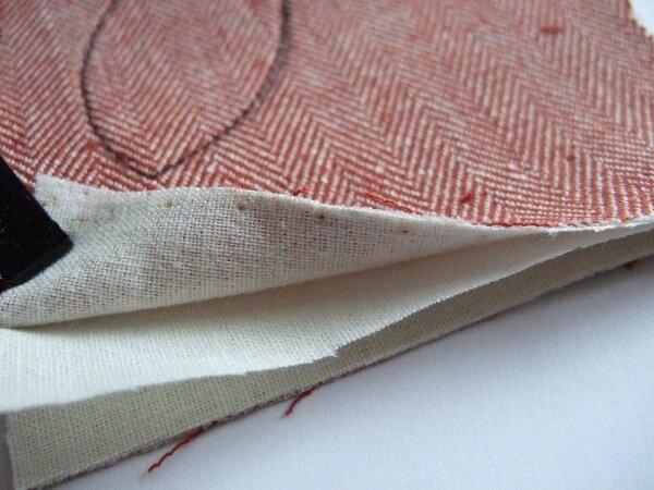 Stoff doppelt mit fester Bügeleinlage bebügelt - hier Baumwollbügeleinlage - einmal längs und einmal quer genommen. Hier ist eine Lage der Bügeleinlage lose, damit man es besser erkennen kann.